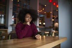 Ttractive młoda kobieta używa nowożytne komórkowe ściąganie multimedii kartoteki od sieci fotografia royalty free
