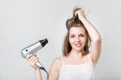 Ttractive teenager blow drying her hair and looking at camera. Portrait of attractive teenager blow drying her hair and looking at camera Stock Photos