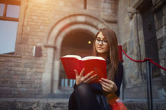 Аttractive young girl read absorbing book at beautiful sunny day. Portrait of a female university student reading interesting book on campus, charming teenager Stock Images