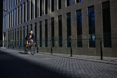 Аttractive young man ride on fixed gear bicycle looking away Royalty Free Stock Images