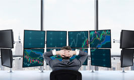 Ttrader at rest in front of screens Stock Image