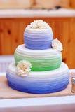 Ttraditional tre tierbröllopstårta med tusenskönablommagarneringar Royaltyfri Fotografi