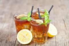 Ttree Glasses Of Traditional Iced Tea With Lemon, Mint Leaves And Ice Cubes On Rustic Wooden Table Stock Photos