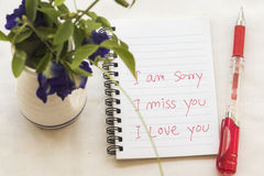 Tu me manque je suis désolé que je t'aime la carte de message écrivent sur le carnet avec des fleurs photographie stock libre de droits