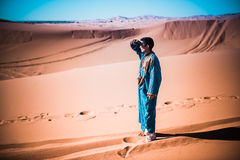 Tuareg in the desert of Sahara. Merzouga, Morocco - 27 March 2015: unidentified tuareg looking for something in the dunes of Sahara desert. Tuareg are called Royalty Free Stock Image