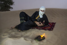 Tuareg man in a desert. Man in traditional Tuareg outfit in a desert, in front of a campfire royalty free stock images