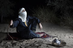 Tuareg man in a desert. Man in traditional Tuareg outfit in a desert, in front of a campfire, making tea stock image