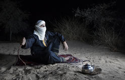 Tuareg man in a desert. Man in traditional Tuareg outfit in a desert, in front of a campfire, making tea royalty free stock images