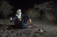 Tuareg man in a desert. Man in traditional Tuareg outfit in a desert, preparing tea royalty free stock photography