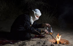 Tuareg man in a desert. Man in traditional Tuareg outfit in a desert, preparing tea royalty free stock photo