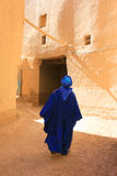 Tuareg man in Rissani. Berber man dressed in traditional Tuareg blue clothing walks through the narrow streest of a ksar in Rissani, Morocco stock images