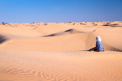 Tuareg man sitting in the Sand dunes desert of Sahara. South Tunisia stock photography