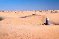 Tuareg man sitting in the Sand dunes desert of Sahara Stock Photography
