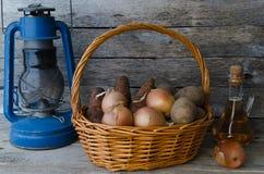 Tubérculos de la patata en una cesta, una zanahoria y una cebolla con aceite de girasol y la lámpara de aceite vieja Fotografía de archivo