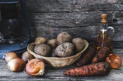 Tubérculos de la patata en una cesta, una zanahoria y una cebolla con aceite de girasol y la lámpara de aceite vieja Imagen de archivo