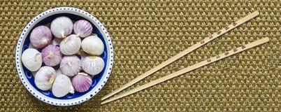 Tubérculos del ajo a solas y de los palillos de madera Imagen de archivo libre de regalías
