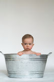 Tub Baby. Image of cute baby sitting in a galvanized tub in front of a white background stock photo