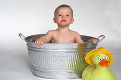 Tub Baby. Image of cute baby sitting in a galvanized tub, with a large rubber duck next to it Royalty Free Stock Photo