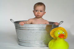 Tub Baby. Image of cute baby sitting in a galvanized tub, with a large rubber duck next to it Royalty Free Stock Photos