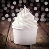 Tub of creamy vanilla or lemon ice cream. Tub of creamy vanilla or tangy lemon ice cream on an old wooden bar counter with a bokeh of festive party lights royalty free stock photography