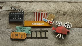 Cinema sign with popcorn bucket movie projector on wood background. Tub of popcorn with a cinema sign with 3d glasses and projector movie tickets on a film strip royalty free stock photos
