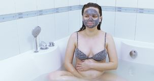 Pregnant with a black mask. The tub pregnant girl with a black cosmetic mask and cucumber on eyes stock video