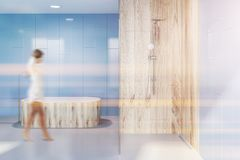 Tub and shower in blue bathroom interior, woman. Woman in modern bathroom with blue walls, white floor, wooden bathtub and shower with wooden and glass walls to stock photography