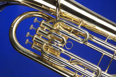 Tuba Euphonium Isolated on Blue. A gold brass tuba euphonium baritone horn isolated against a blue background in the horizontal format Royalty Free Stock Photos