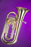 Tuba Euphonium Isolated on Purple. A gold brass tuba euphonium baritone horn isolated against a spotlight purple background  in the vertical format Royalty Free Stock Photos