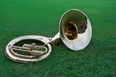 Tuba lying on the grass. As the marching band practices off to the side, a tuba is resting in the grass of the football field Stock Images