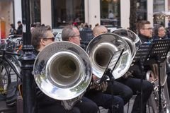Tuba musicians from a brass band playing outside in a town market square and spectators are standing listening. Copenhagen, Denmark - May 4, 2019 royalty free stock photo