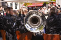 Tuba musicians from a brass band playing outside in a town market square and spectators are standing listening. Copenhagen, Denmark - May 4, 2019 royalty free stock image