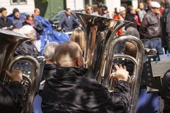 Tuba musicians from a brass band playing outside in a town market square and spectators are standing listening. Copenhagen, Denmark - May 4, 2019 stock images
