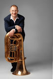 Tuba Player. Portrait  of a  smiling young tubaist with his instrument Royalty Free Stock Photography