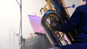 Tubaist in an orchestra on the stage, holds big brass tube, behind the scenes close-up shoot stock video footage