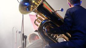 Tubaist in an orchestra on the stage, holds big brass tube, behind the scenes shoot stock video footage