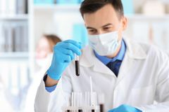 Tube à essai de participation de scientifique avec l'échantillon dans le laboratoire photo stock