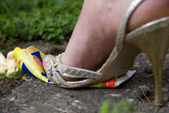 Tube. Female feet dressed in fashion shoes and socks, crushing a mayonnaise tube Royalty Free Stock Images