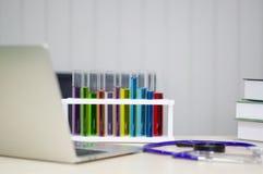 Tube de verre coloré placé près de l'ordinateur portable dans le laboratoire avec le concept de la recherche et de l'invention de image stock