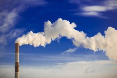 Tube factory smoke. Smoke from a pipe on a background of blue sk Stock Photo