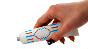 Tube in hand. Woman's hand holding a tube on the white background Royalty Free Stock Images