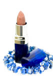 Tube of lipstick and blue bracelet. A tube of lipstick is surrounded by a beautiful blue stone bracelet with white background Stock Images