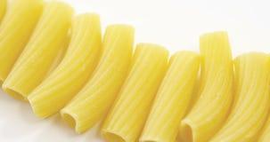 Tube pasta on white background. Close-up of tube pasta on white background stock video