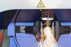 The tube or pipe laser cutting machine. While cutting the tube or pipe with the sparking light Royalty Free Stock Photos