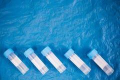 tube pour prélever le matériel biologique sur un fond bleu, vue supérieure photo libre de droits