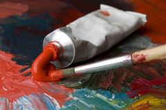 Tube of red paint. With a brush Royalty Free Stock Images