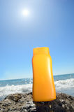 Tube with sun protection on beach of ocean Royalty Free Stock Photo