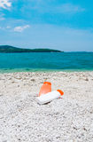 Tube with sun protection on a pebble beach Royalty Free Stock Photo