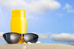Tube with sun protection and sunglasses on beach Stock Photos