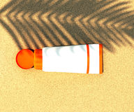 Tube of sunscreen on beach sand Stock Images